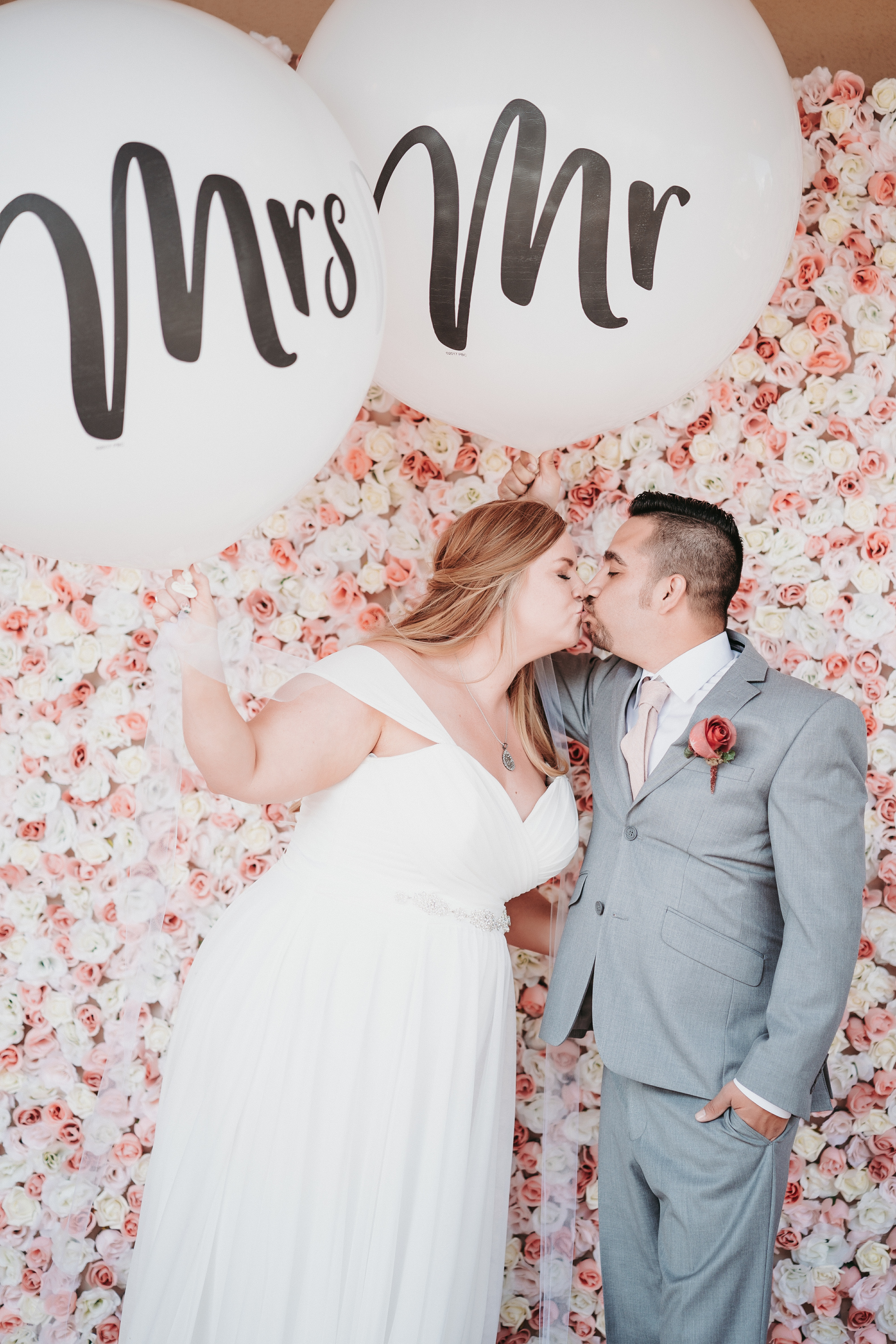 balloons, mr and mrs balloons, floral backdrop, bride and groom kiss, new mexico wedding decor, casi sueno, pink and white flowers